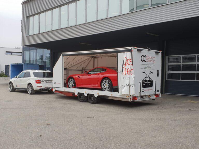 Auto auf Transportanhänger mit Zugfahrzeug Mercedes und Ferrari